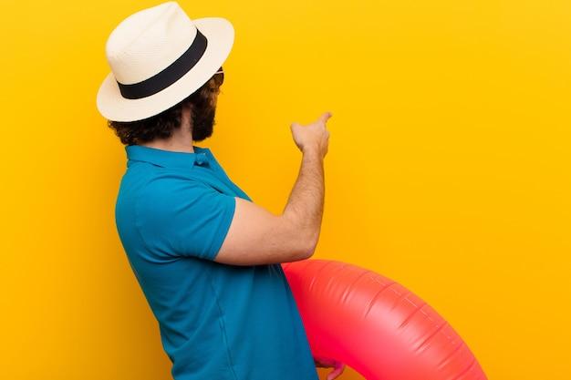 Jeune homme fou, debout, pointant objet, espace copie, vue postérieure
