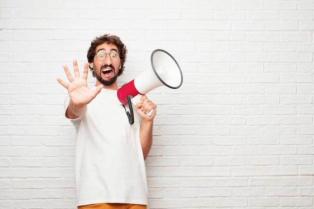 Jeune homme fou avec un mégaphone contre le mur de briques.
