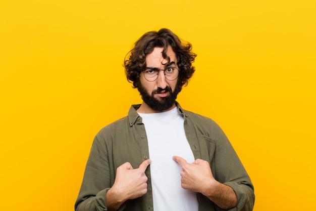 Jeune homme fou pointant sur lui-même avec un regard confus et interrogateur, choqué et surpris d'être choisi contre un mur jaune