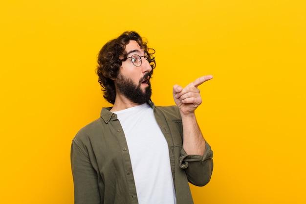 Jeune homme fou se sentant choqué et surpris, pointant le regard et levant les yeux émerveillé par le regard étonné et bouche bée contre le mur jaune