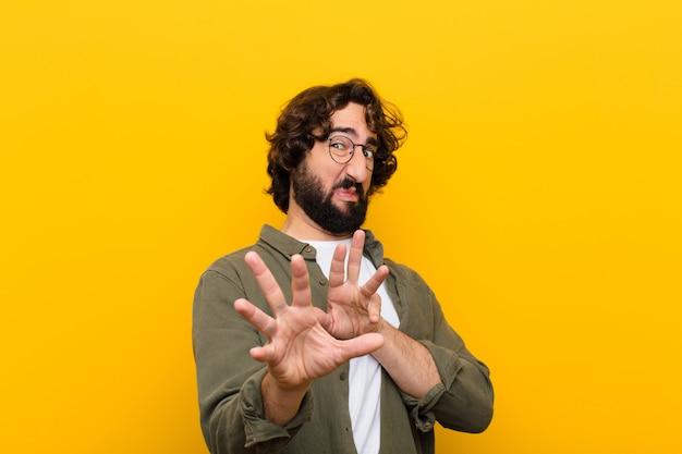 Jeune homme fou se sentant dégoûté et nauséeux, s'éloignant de quelque chose de méchant, puant ou puant, disant beurk contre un mur jaune