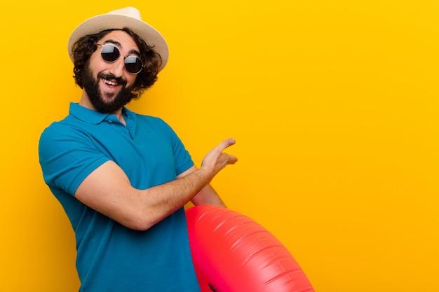 Jeune homme fou se sentant heureux et joyeux, souriant et accueillant, vous invitant à un geste amical du mur orange