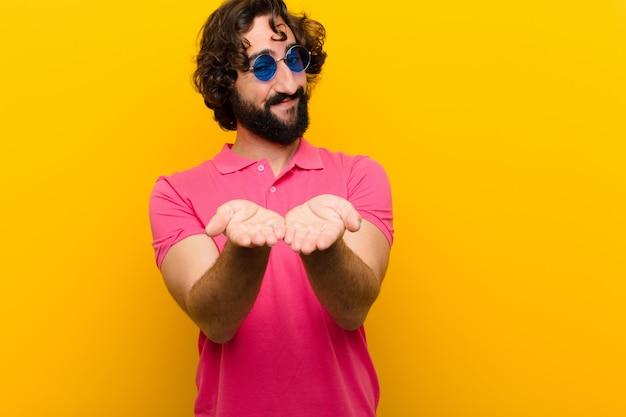 Jeune homme fou souriant joyeusement avec un regard amical, confiant et positif, offrant et montrant un objet mur orange
