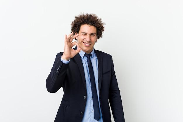 Jeune homme frisé d'affaires contre le mur blanc fait un clin d'œil et détient un geste correct avec la main.