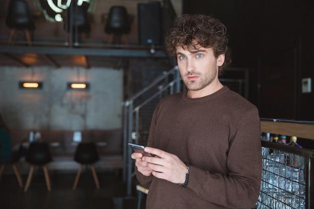 Jeune homme frisé pensif rêvassant bel homme tenant un téléphone portable et l'utilisant dans un café