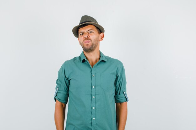 Jeune homme fronçant les sourcils et regardant la caméra en chemise