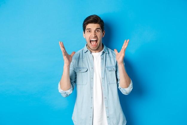 Jeune homme frustré criant et ayant l'air tendu, serrant la main folle, debout sur fond bleu