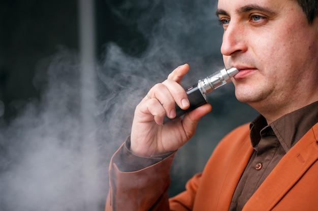 Jeune homme fumant une cigarette électronique