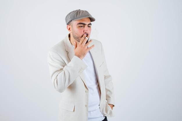 Jeune homme fumant des cigarettes tout en tenant les mains sur la taille en t-shirt blanc, veste et casquette grise et à la sérieuse