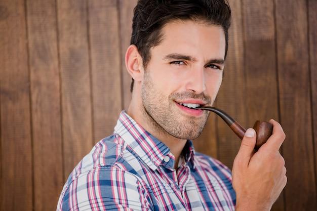 Jeune homme fumant la pipe