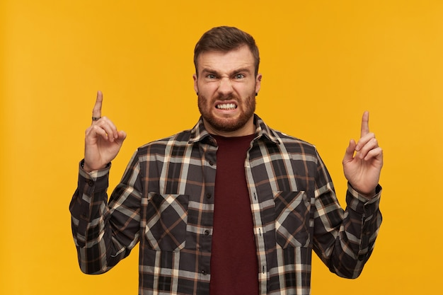 Jeune homme furieux fou en chemise à carreaux avec barbe pointant vers le ciel à deux mains et regardant à l'avant sur le mur jaune