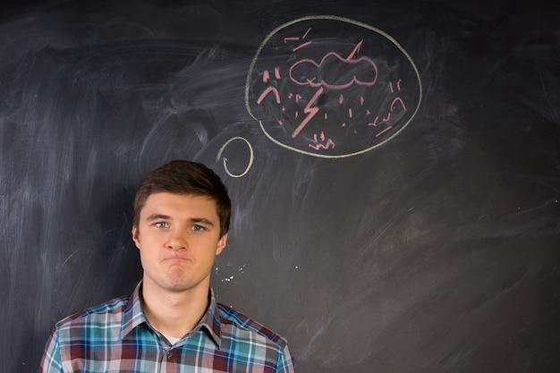 Jeune homme furieux regardant avec colère la caméra avec une bulle de pensée dessinée à la main au-dessus de sa tête sur un tableau noir montrant un coup de foudre et un éclair