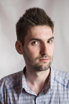 Jeune homme gai attrayant aux cheveux noirs avec une barbe dans une chemise sur un fond blanc. style masculin. portrait masculin