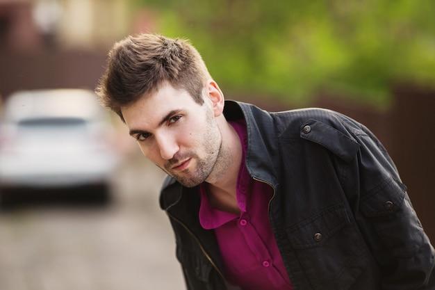 Jeune homme gai attrayant aux cheveux noirs avec une barbe portant une chemise et une veste noire dans la rue. style de rue masculin. la nature au printemps. se promener dans la ville.