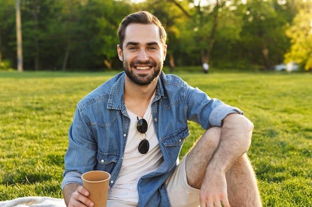 Jeune homme gai ayant un pique-nique au parc, tenant la tasse
