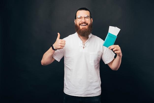 Jeune homme gai avec la barbe tenant le passeport avec des billets d'avion et montrant le pouce vers le haut