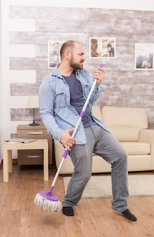 Jeune homme gai chantant et nettoyant la maison