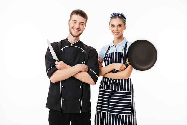 Jeune homme gai chef en uniforme noir avec couteau à la main et jolie femme cuisinier en tablier rayé et casquette avec casserole à la main heureusement