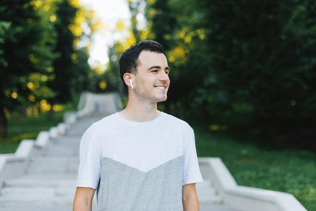 Jeune homme gai frais à la recherche de suite, marchant dans le parc le matin.