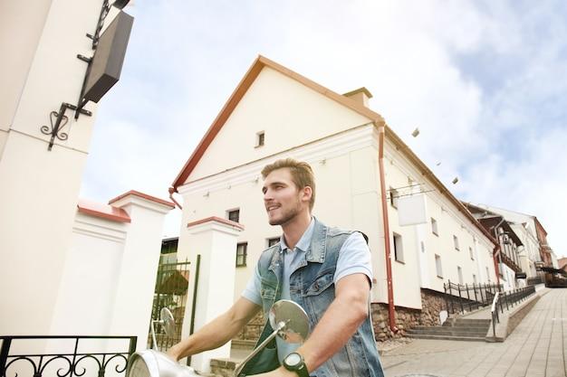 Le jeune homme gai monte sur le scooter en ville