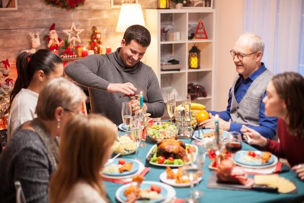 Jeune homme gai ouvrant une bouteille de vin au dîner de famille de noël.