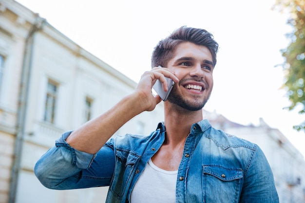 Jeune homme gai parlant au téléphone portable dans la ville