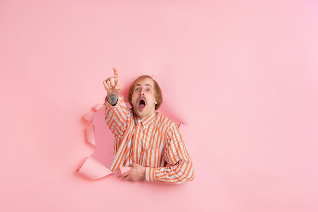 Un jeune homme gai pose dans un mur de trou de papier de corail déchiré émotionnel et expressif