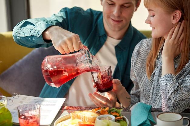 Jeune homme galant verse une boisson de jus sucré dans des verres pour femmes