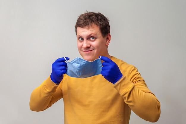 Un jeune homme en gants met un masque médical. concept de coronavirus et de covid-19