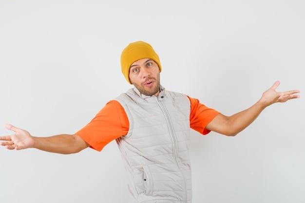 Jeune homme gardant les bras grands ouverts en t-shirt, veste, vue de face de chapeau.