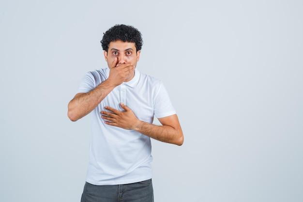 Jeune homme gardant la main sur la bouche en t-shirt blanc, pantalon et l'air choqué. vue de face.