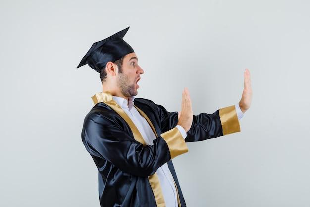 Jeune homme gardant les mains pour se défendre en uniforme diplômé et à la peur. .