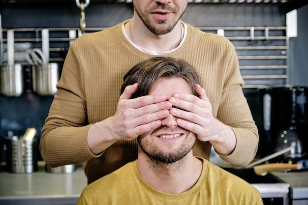 Jeune homme gardant les mains sur les yeux de son petit ami dans la cuisine
