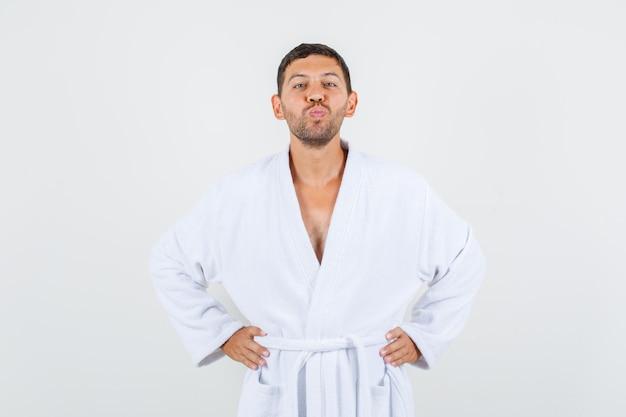 Jeune homme gardant ses lèvres pliées en peignoir blanc et à la joyeuse vue de face.