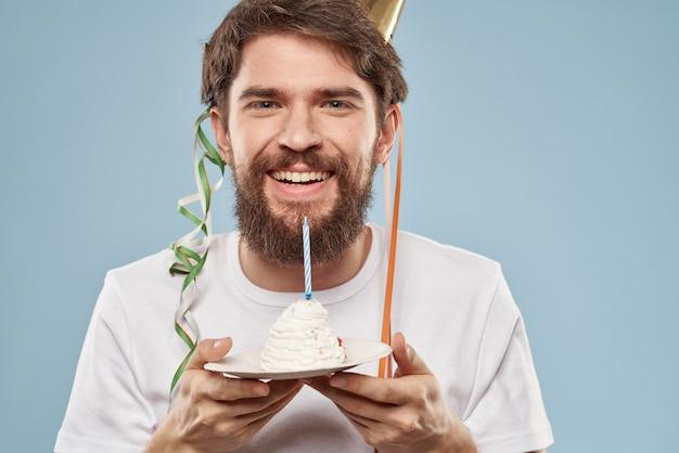 Jeune homme avec un gâteau de fête avec des tranches célèbre un anniversaire dans un bonnet