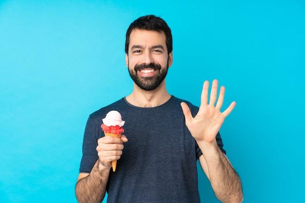 Jeune homme avec une glace au cornet sur un mur bleu isolé comptant cinq avec les doigts