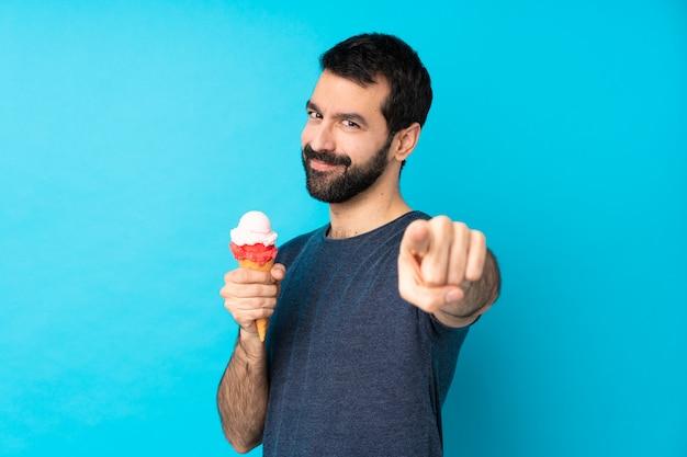 Jeune homme avec une glace au cornet sur le mur bleu isolé pointe du doigt vers vous avec une expression confiante