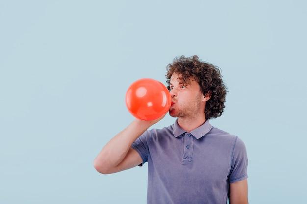 Jeune homme gonfle un ballon rouge
