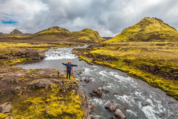 Un jeune homme sur une grande rivière à partir de la randonnée de 54 km de landmannalaugar, islande