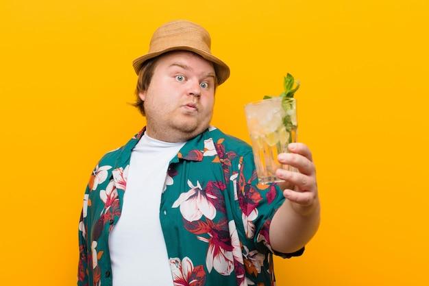 Jeune homme de grande taille avec un verre de mojito contre un mur plat