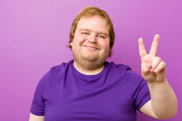 Jeune homme gras authentique jeune rousse montrant le numéro deux avec les doigts.