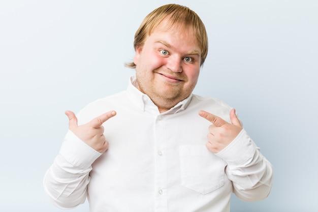 Jeune homme gras rousse authentique sourit, pointant du doigt la bouche.