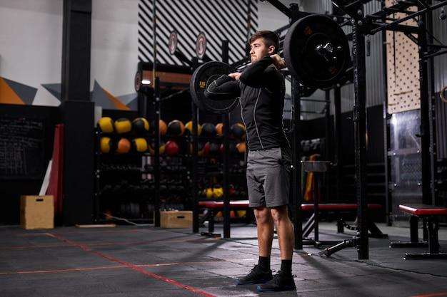 Jeune homme avec de gros muscles tenant un poids lourd pour cross fit swing entraînement entraînement de base dur dans la salle de gym, portant des vêtements sportifs, seul. portrait