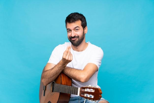 Jeune homme avec une guitare au cours d'un geste d'argent faisant isolé