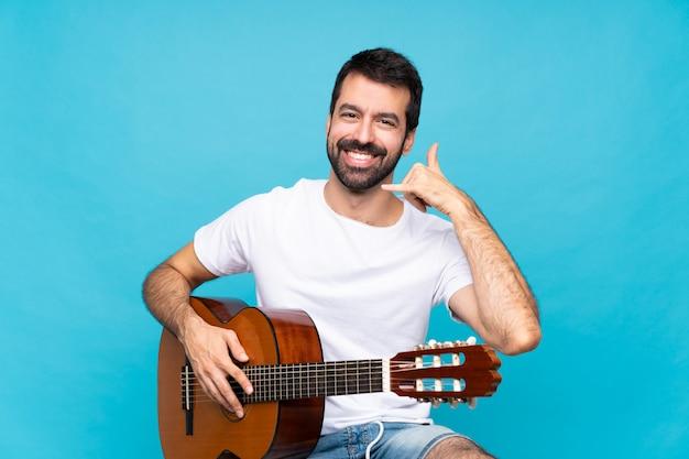 Jeune homme avec guitare sur bleu isolé, geste de téléphone. rappelle-moi