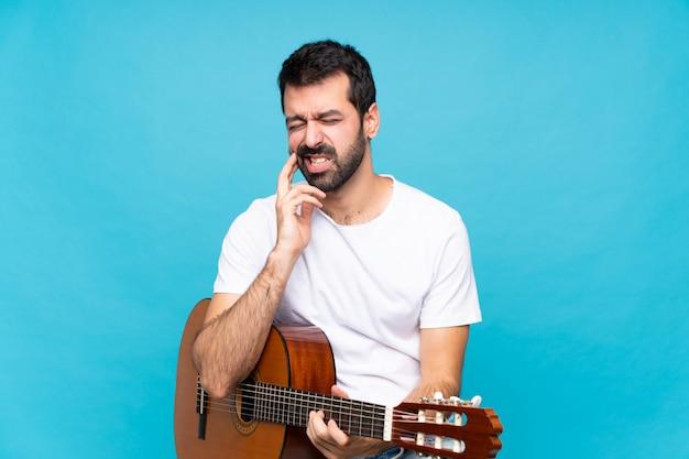 Jeune homme avec guitare sur bleu isolé avec mal aux dents