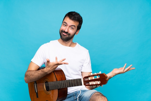 Jeune homme avec guitare sur bleu isolé s'étendant les mains sur le côté pour inviter à venir