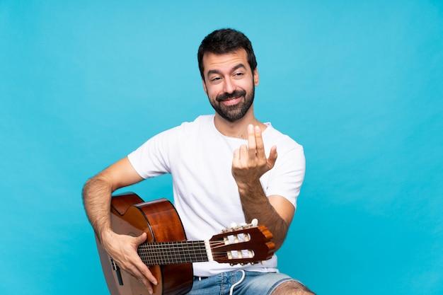 Jeune homme avec guitare invitant à venir avec la main. heureux que tu sois venu
