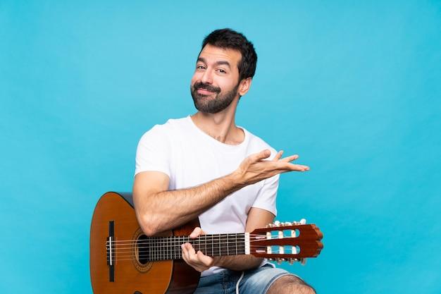 Jeune homme avec une guitare sur un mur bleu isolé, présentant une idée tout en regardant souriant
