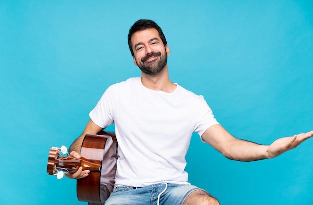Jeune homme avec guitare sur mur bleu isolé présentant et invitant à venir avec la main